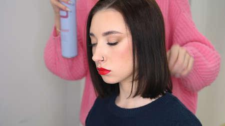 Hair master sprays varnish, makes styling. Attractive brunette in beauty salon.