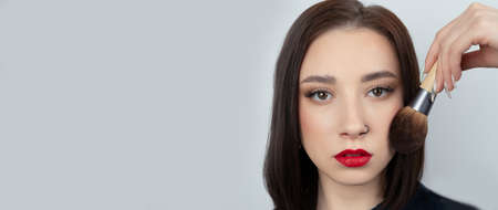 Young woman with makeup brush near at face. Beautiful girl with perfect skin, red lips and a pierced nose