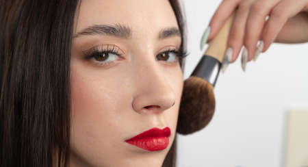 Young woman with makeup brush near at face. Beautiful girl with perfect skin and red lips, close up 版權商用圖片