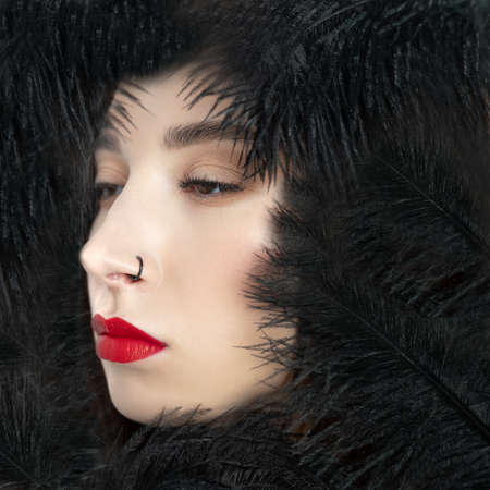 Creative stylish portrait of caucasian model girl with red lips and black feathers around her head. Beauty concept.