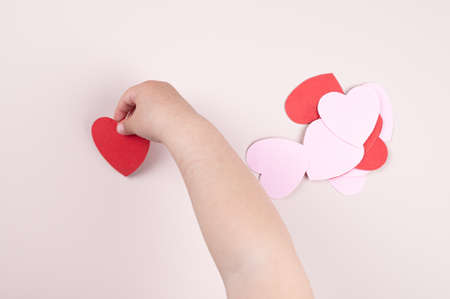 Child and love. holding a heart in his hand. Mothers Day.