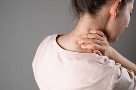 A woman has a sore neck after a hard day at work.