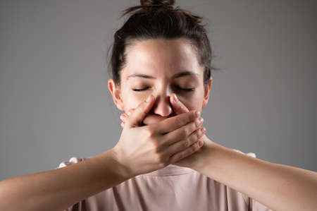 The woman covers her mouth with her hands. 版權商用圖片