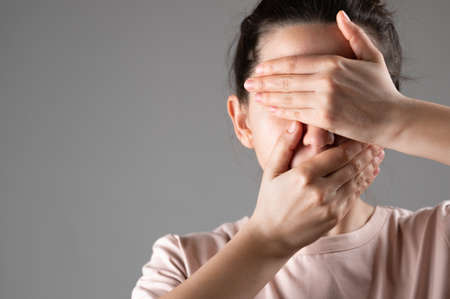 The woman covers her mouth and eyes with her hands.