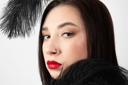 Creative stylish portrait of caucasian model girl with red lips and black feathers around her head, side view. Beauty concept.