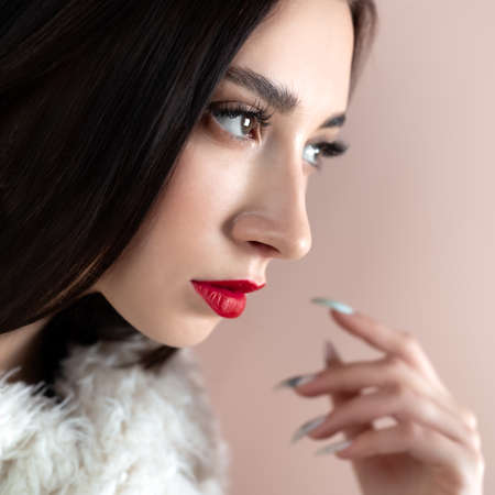 Young woman with great shapes brows, long eyelashes and red lips. Brunette posing on white wall.