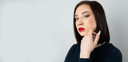 Portrait of a young beautiful brunette with piercings in her nose. On an isolated background.