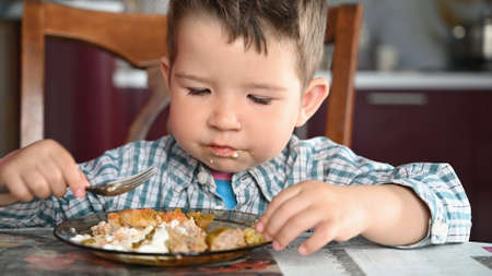 Child in shirt eating close up.