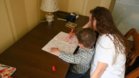 A young mother paints with felt-tip pens with a child.