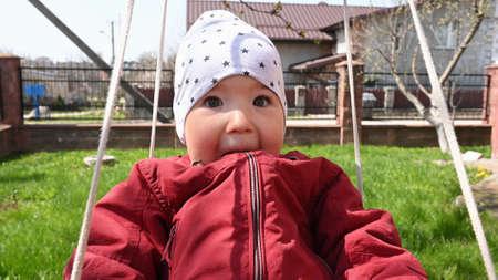 Joyful child riding on a swing, close-up.