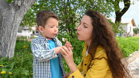 Mom and child blow out a dandelion.