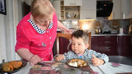 Caring grandmother with her grandson eat. Reklamní fotografie