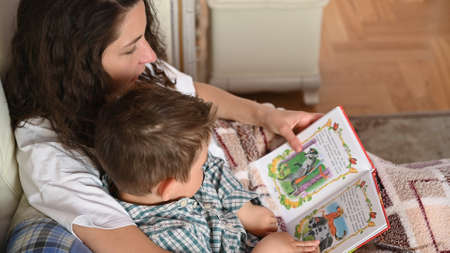 Young mother reads a book to her child before bedtime.