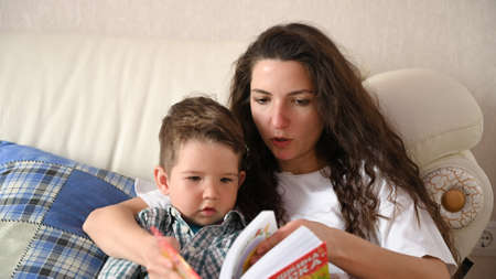 Young mother is engaged in the education of the child.