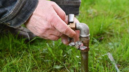 Man Fixing Garden Water Pipe.