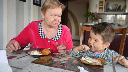Grandmother and grandson eat at the table. Reklamní fotografie