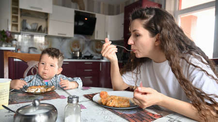 Young mother eating in the kitchen sitting at the table. Reklamní fotografie