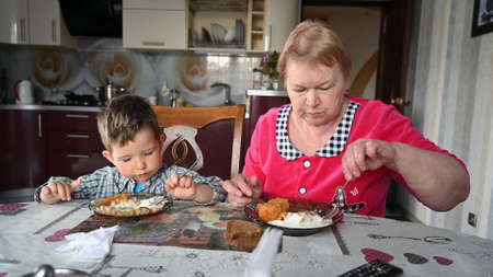 grandmother feeds her grandson in the kitchen.