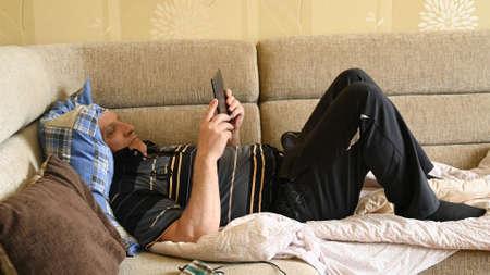 Elderly man resting at the tablet.