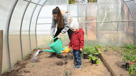 Mom and child are watered from a watering can in a greenhouse.
