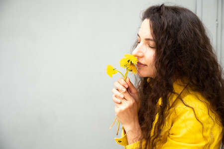 Young woman with curly hair with dandelions in her hands.