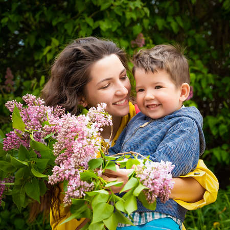 Happy mom with baby with flowers. 版權商用圖片