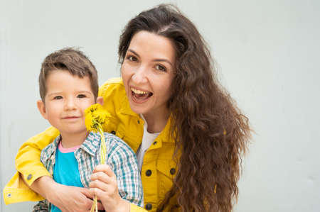 Young mother with curly hair and a child holding flowers. 版權商用圖片