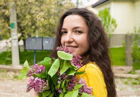 Young girl with curly hair with lilacs in her hands.