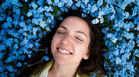Beautiful young girl smiling on a background of blue flowers. 版權商用圖片