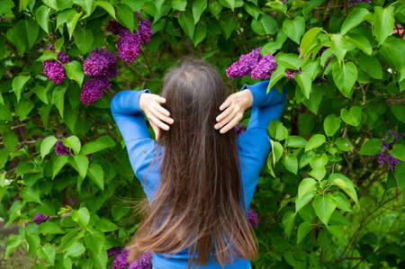 Beautiful young girl with beautiful hair near the lilac. 版權商用圖片