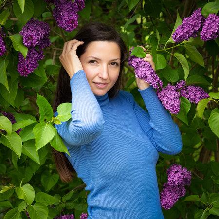 Beautiful young girl near the lilac.