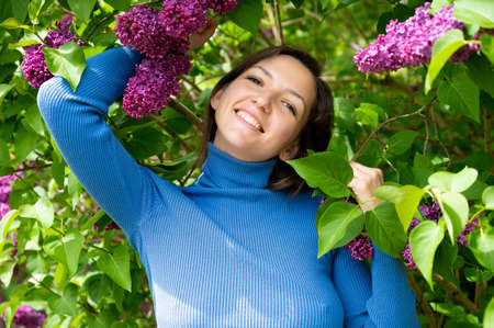 young girl near lilac flowers. 版權商用圖片