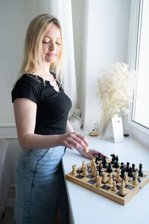 Woman near the chessboard. Woman thinking about strategy. 版權商用圖片