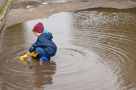 The child is playing in a large puddle. on the roadway Archivio Fotografico