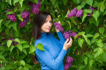 young girl near lilac flowers