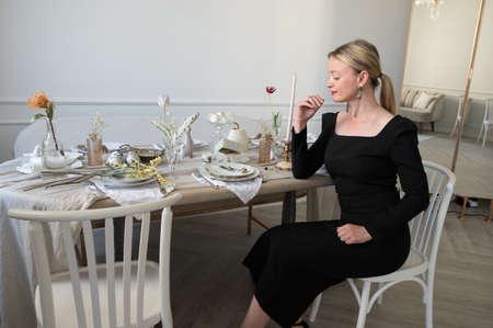 Elegant woman in black dress sits at the table. 版權商用圖片
