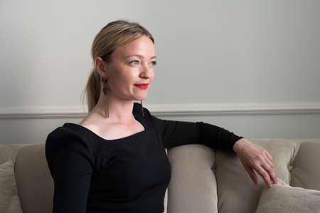 Elegant woman in black dress sits on the sofa.