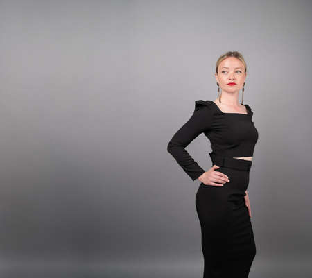 Beautiful blonde in a black dress on an isolated background. 版權商用圖片
