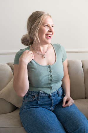Plump woman laughs while sitting on the couch. 版權商用圖片