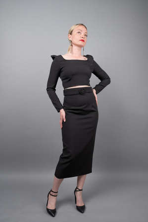 Woman in black dress on gray background. 版權商用圖片