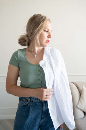 The woman is showing off a white shirt