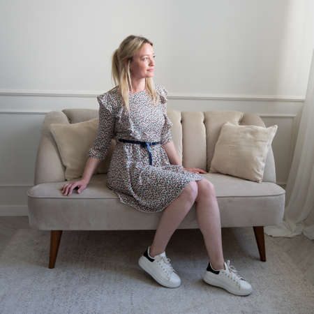 A woman in a summer dress is sitting on the sofa.