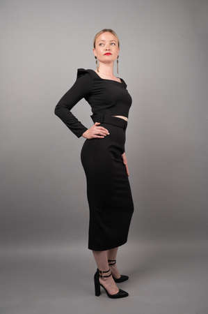 Strict business woman on gray background.
