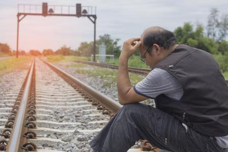 Les hommes qui désespèrent Assis sur les voies ferrées Banque d'images - 66486383