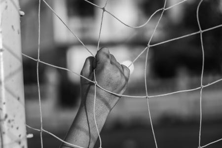 terrain de handball: Hand holding football goal net.