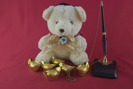 Teddy Bear and gold Chinese on red background. Translation in English meaning lucky and richly