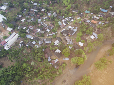 Aerial photos of small towns In Thailand, surrounded by arid fields, there is a road through.