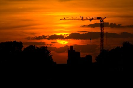silhouette of a crane with a red sunset in the back photo