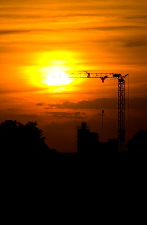 sunset with silhouette of a crane and factory photo