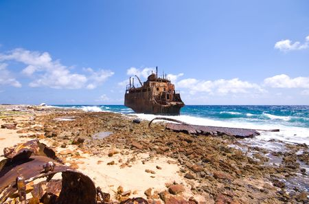wonky: rusty caribbean shipwreck washing ashore on little curacao